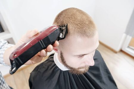 Barber shaves the clients head with a red electric trimmer. view from above, selective focus