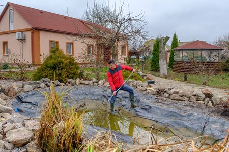 white man cleans an artificial garden pond with a landing net from slime, falling leaves and catches fish for resettlement in an aquarium near his house. Autumn seasonal pond care before winter