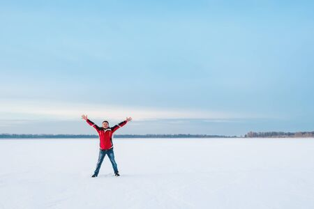 A happy smiling man with wide outstretched arms in the direction of clear sky, stands on the snowy surface of the frozen lake