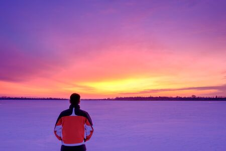 A man stands with his back to the camera on the snowy surface of a frozen lake and watches colorful twilight. Copy spave
