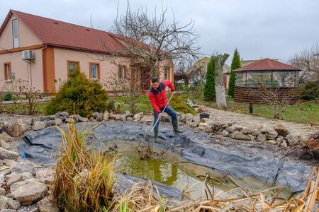 white man cleans a garden pond with a landing net from slime, water plants, falling leaves and catches fish for resettlement in an aquarium near his house. Autumn seasonal pond care before winter