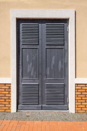 Closed old grey doors on background of yellow wall. front view from street