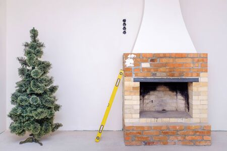 christmas tree, water level and unfinished fireplace in the renovated room. Repair or new building concept Stock fotó