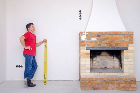 A white man stands with a yellow water level in his hands and looks thoughtfully at the unfinished fireplace. The concept of repair or new building
