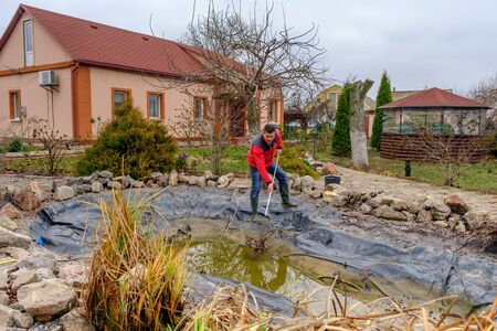 white man cleans a garden pond with a landing net from slime, water plants, falling leaves and catches fish for resettlement in an aquarium near his house before winter