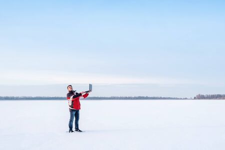 A white man in warm jacket works with a laptop standing on the surface of a frozen lake.