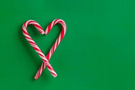 Two christmas red and white candy canes in the shape of heart on a green paper background. Copy space for text. Stock fotó