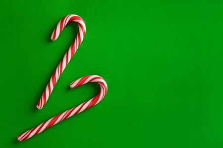 Two christmas red candies on a green paper background. Copy space for text.