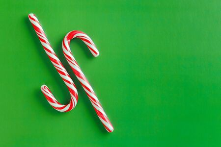 Two christmas red and white candy canes on a textured green paper background. Copy space for text. Stock fotó