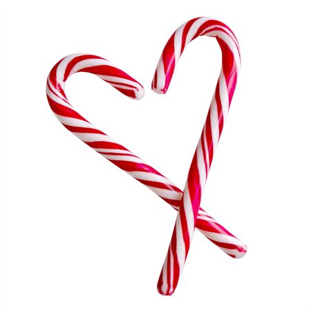 Two christmas red and white candy canes in the shape of heart isolated on white background.