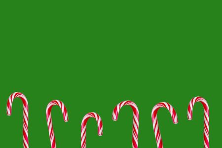 Festive christmas red and white candy canes isolated on green christmas background.Flat lay, copy space for text