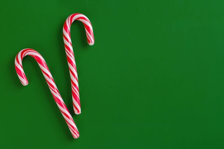Two christmas red and white candy canes on green paper background. Copy space for text. Banque d'images - 135503328