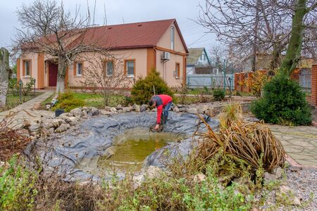 white man cleans a garden pond with a landing net from slime, water plants, falling leaves and catches fish for resettlement in an aquarium. Autumn seasonal pond care before winter