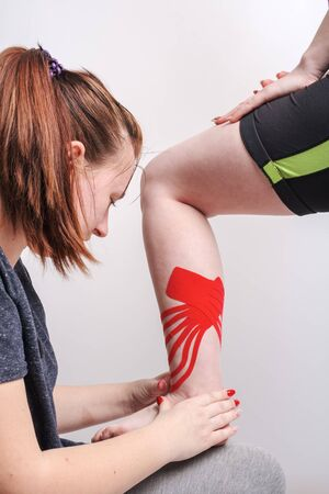 physio and kinesiology therapy techniques performed by a female physiotherapist on a leg female patient