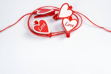 rolled red rope with red and white clothespins in shape of hearts on a white background. Valentine's Day concept. Greeting card with copy space for your text or advertising