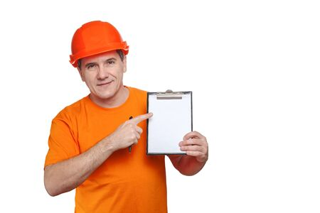 Portrait smiling middle-aged handsome worker wearing orange hard hat holding blank paper sheet in clipboard, showing finger to copy space for text, isolated on white background
