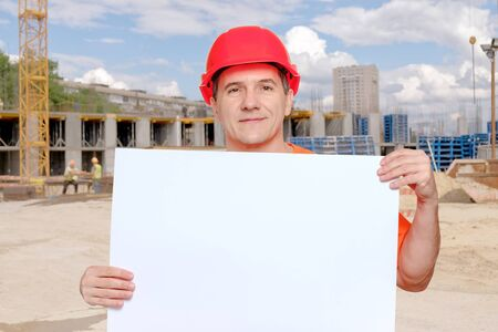 Portrait smiling middle-aged handsome worker wearing red hard hat holding blank paper sheet in hands. Copy space for text, on construction site background