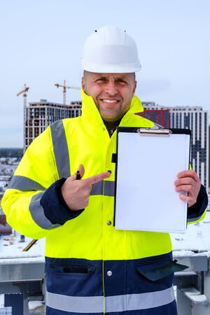 A smiling caucasian builder wearing white helmet and a yellow vest stands on the roof, holds clipboard and pointing finger to blank paper sheet, copy space for your text. Stock Photo