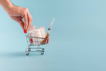 male hand pushing shopping cart full of pills on blue background close up. e-commerce, online drugstore business, delivery concept. Copy space for text or advertising Stok Fotoğraf