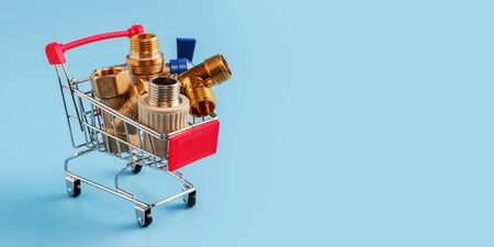 red shopping cart with plumbing fittings closeup. Brass ball valve, y filter, tee and polypropylene coupling in mini basket on blue background. shopping concept, copy space