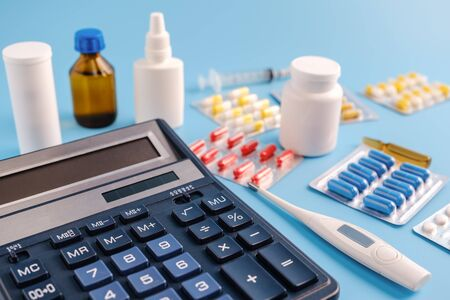 Calculator, thermometer and pile of drugs on blue background. cost of health care concept