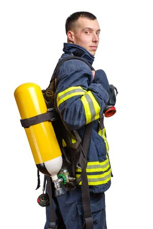 Young caucasian firefighter posing in profile with Full Facepiece Respirator and Breathing Air Cylinder Assembly on his back in fireproof uniform isolated on white background Banque d'images