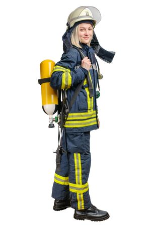 Young woman firefighter wearing uniform and helmet with Breathing Air Cylinder Assembly and Full Facepiece Respirator on her back isolated on a white background Archivio Fotografico