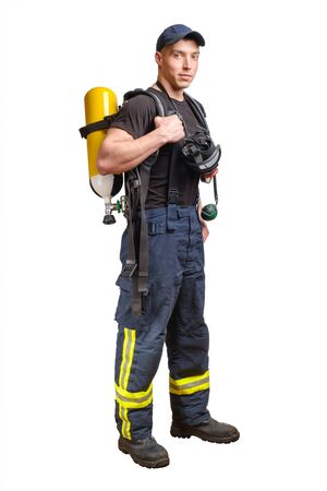 Young fireman in baseball cap with respirator and air breathing apparatus on his back in protective pants and black t-shirt isolated on white background.