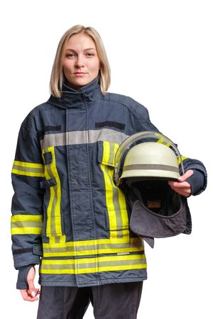 young caucasian woman firefighter in fireproof uniform stands and looks at the camera with helmet in her hands. Isolated on white