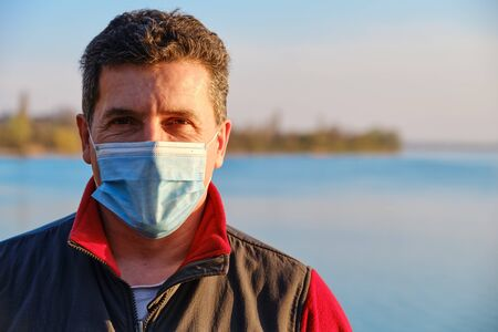 Mature caucasian man wearing protective surgical face mask to prevent coronavirus, on the lake background. Close Up portrait, copy space