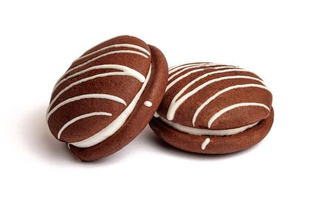Two chocolate whoopies pies with marshmallow filling isolated on white background. Foto de archivo