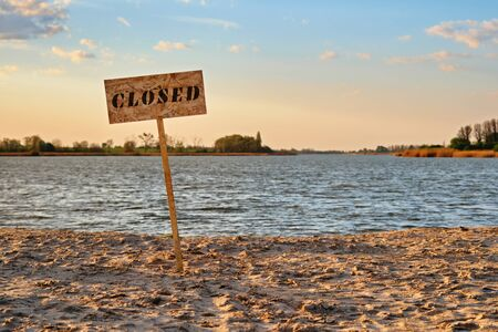 Signpost with inscription closed along the sand beach of the river. Contaminated water, quarantine, virus outbreak, access fee limitation concept