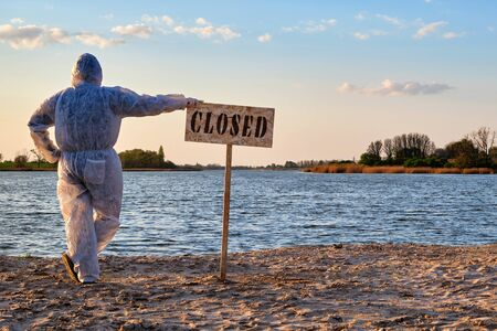 Male wearing protective suit stands with his back near warning sign with inscription closed along the sand beach of the river. Contaminated water, quarantine, virus outbreak, crime scene concept