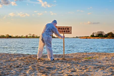 Male wearing protective suit stands with his back near warning sign with inscription beach closed along the sand beach of the river. Contaminated water, quarantine, virus outbreak, crime scene concept