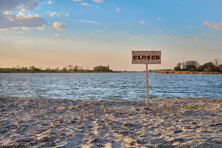 Signpost with inscription closed along the abandoned sand beach river. Contaminated water, quarantine, virus outbreak, access fee limitation concept.