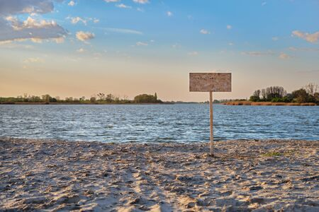 Signpost with copy space for text along the sand beach of the river. Contaminated water, quarantine, virus outbreak, access fee limitation concept.