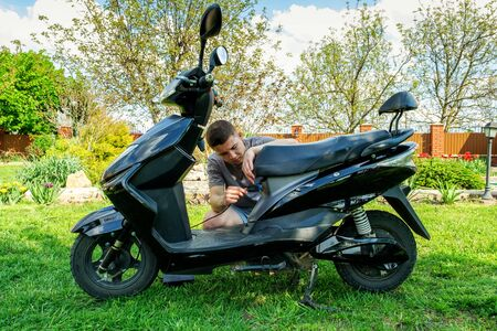 teenager inserts plug into the charging socket of electric scooter on the lawn in the courtyard of his house.