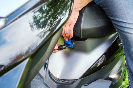 man sits on a seat and his hands insert a plug into the charging socket of an electric scooter. Close up view Stockfoto