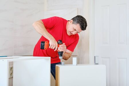 middle aged white repairmanman screwed the cabinet legs into wooden furniture with cordless screwdriver.