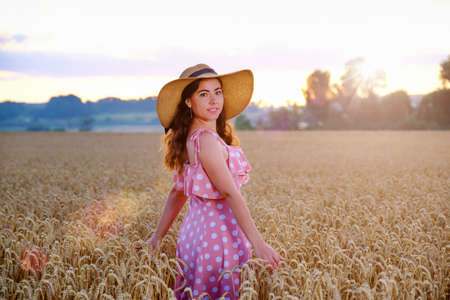 Young woman in straw hat stands turning around on a background of wheat field and smiling