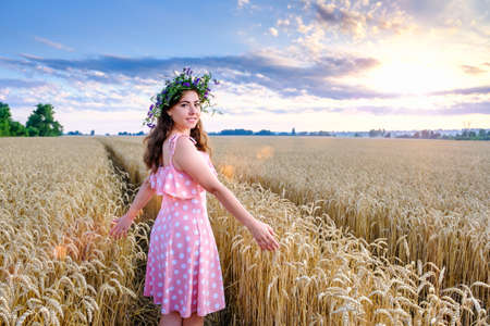 Young woman with flower wreath on head stands turning around on a background of wheat field and smiling