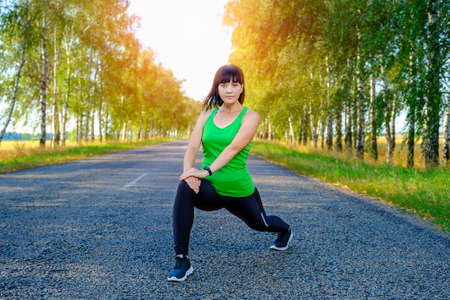 Young caucasian woman stretching legs before jogging on asphalt road in countryside, warming up for muscles. Banque d'images