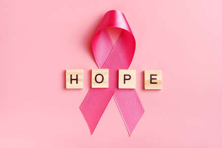 Pink ribbon and wooden letters with word hope on pink background. Stock Photo