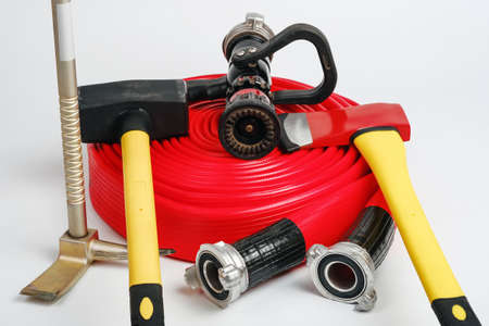 Red rolled fire hose, hooligan pinch-bar, large yellow sledgehammer and ax from firefighter's toolbox on white background. Closeup view, selective focus Фото со стока