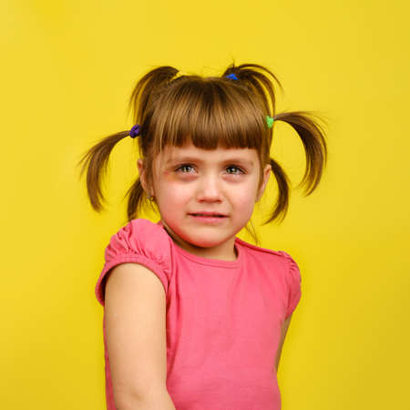 Portrait of crying little caucasian girl with pigtails and bruise under the eye on yellow background.
