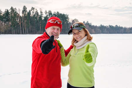 Closeup smiling senior couple resting while walking and showing thumb up on snowy frozen lake. Elderly wife and husband doing healthy exercise outdoors. Active lifestyle after retirement concept.