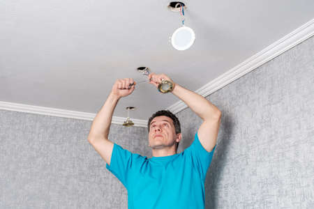 Middle-aged caucasian electrician removes old, inefficient halogen lamps from the ceiling and replaces them with modern LED ceiling spotlights.