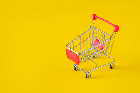 Empty red shopping cart on yellow background, mini metal cart isolated on yellow background, copy space for text