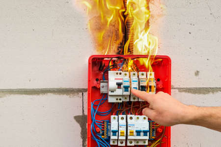 Finger of male hand turns off burning switchboard from overload or short circuit on wall closeup. Circuit breakers on fire from overheating due to poor connection or poor quality wires. Stock Photo