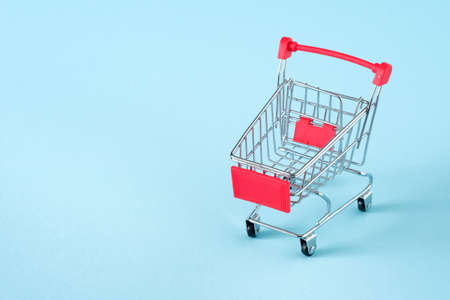 Empty red shopping cart on blue background, mini metal cart isolated on yellow background, copy space for text